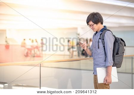 Young Asian man dressed in casual style using smartphone and holding laptop computer in shopping mall modern IT lifestyle with work life balance concept