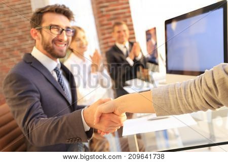 businessman shaking hands with a business partner sitting near your desktop
