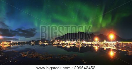 Northern lights over pier in Norway. Aurora borealis in night starry sky above fjord. Night scene with bright northern lights.