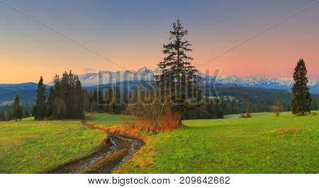 Morning in green valley. Green valley on snowy mountains background in dawn. Famous touristik place in Poland Zakopane.