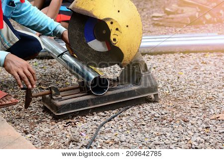 A Man Using A Steel Cutter Machine On Construction Site Ground