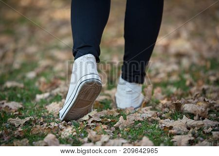 Woman In White Sneakers On The Grass