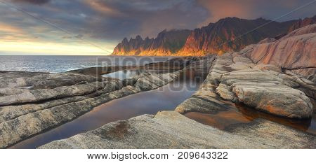 Stone rocks and beaches of Norway. Gorgeous sunset on Norway seaside. Beautiful norwegian seascape.