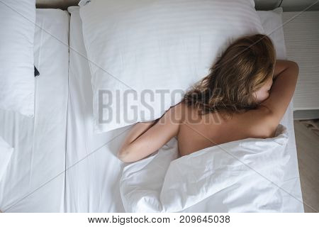Young calm woman lying on white sheet in bed sleeping in peace back view