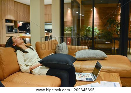 Business Woman Sleeping On Sofa In Living Room At Night