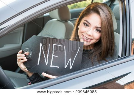 Happy teen girl driving a new car
