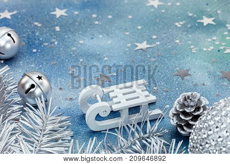 Silver Jingle Bells And Christmas Tree Branches With White Sledge On Blue Background