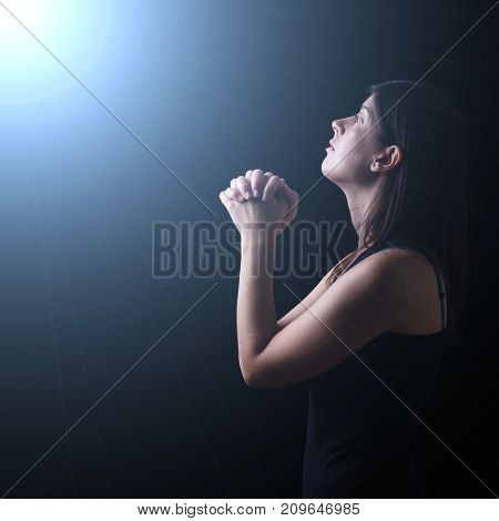 Faithful woman praying in worship to god looking up in hope, under a divine or celestial light. Concept for religion, faith, prayer and spirituality.