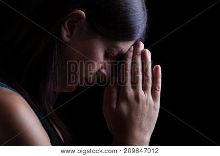 Faithful woman praying, with hands folded in worship touching the forehead, head down and eyes closed in religious fervor, on black background. Concept for religion, faith, prayer and spirituality.  poster