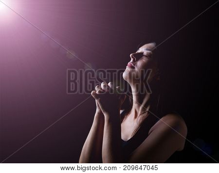 Faithful woman praying under a divine or celestial light and feeling the presence or being touched by god. Hands folded in worship, head up and eyes closed in religious fervor. Black background.