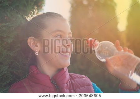 Beautiful girl is drinking water the hot sun in the park. Healthily concept. Healthy lifestyle concept. copy space. Portrait happy smiles beautiful girl . Portrait smiles girl. girl drinking water