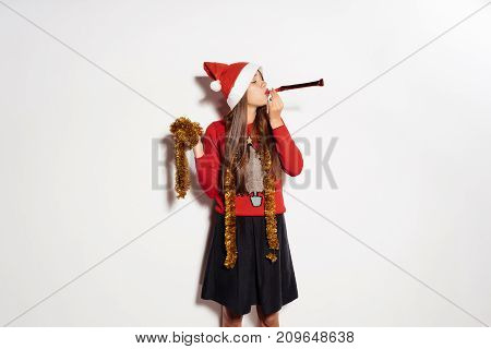 beautiful young happy girl celebrating new year and christmas in a red cap and gold tinsel