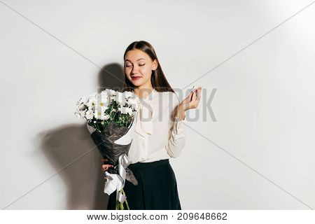 beautiful young happy girl celebrates something, holds a bouquet of white flowers in hands