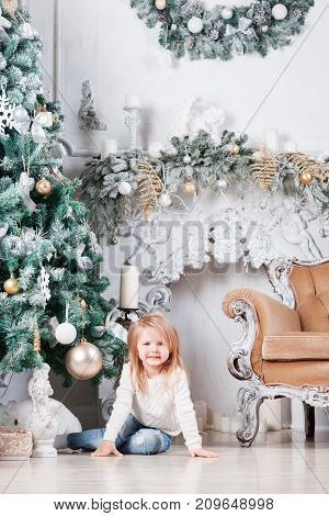 Adorable little blonde girl in a white dress sitting on a floor near christmas tree and looking on toy. Pretty kid in a warm cozy room with candle lights. New year photo. Art work.