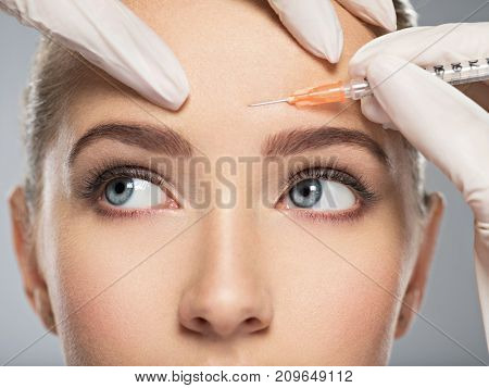 Portrait of young Caucasian woman getting cosmetic injection in forehead. Beautiful woman gets botox injection in her face.