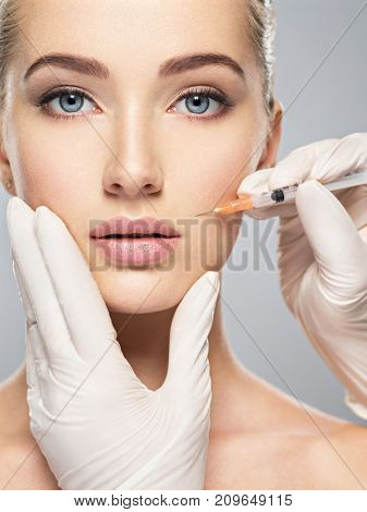 Woman getting cosmetic injection of in cheek, closeup. Woman in beauty salon. plastic surgery clinic.