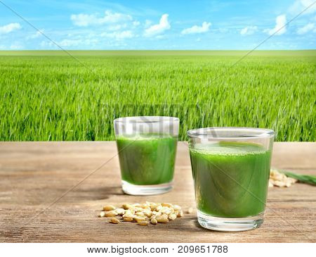 Glasses of juice and wheat grass field  on background