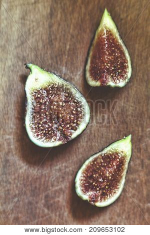 Ripe and delicious figs. Pieces of figs on a wooden board closeup. Macro. View from above.