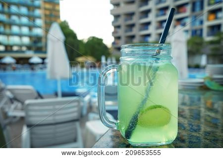 Glass mason jar with fresh drink on table outdoors