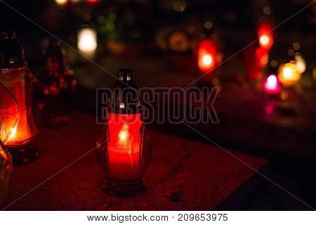 Burning Colourful Candles On Cemetery At Night.