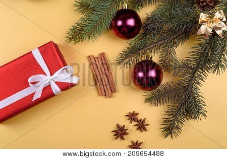 Christmas background with red gift boxe fir tree branches with glass balls pine cones cinnamon sticks and stars anise on golden background free space. Flat lay top view with copy space