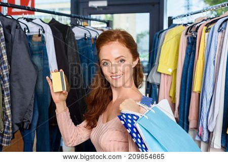 beautiful woman with shopping bags and credit card in boutique