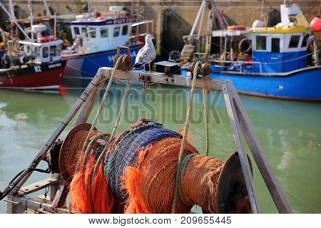 WHITSTABLE, UK - OCTOBER 15, 2017: Close-up on a seagull and a capstan at the fishing Harbor with fishing boats in the background