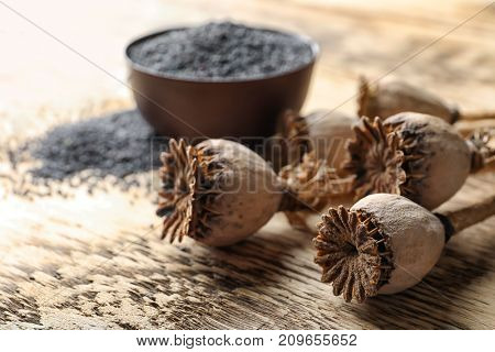 Dried poppy heads and seeds in bowl on table, closeup