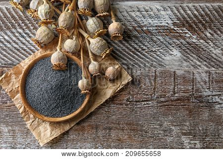 Poppy heads and plate with seeds on wooden table