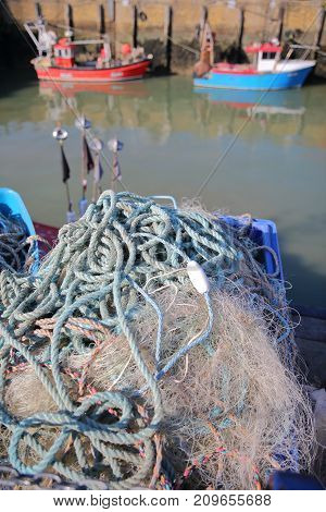 Close-up on fishing nets at the fishing Harbor with fishing boats and in the background, Whitstable, UK