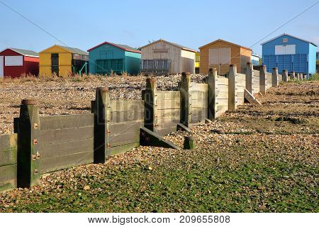 WHITSTABLE, UK - OCTOBER 15, 2017: A row of colorful wooden Huts overlooking the sea with breakwater in the foreground