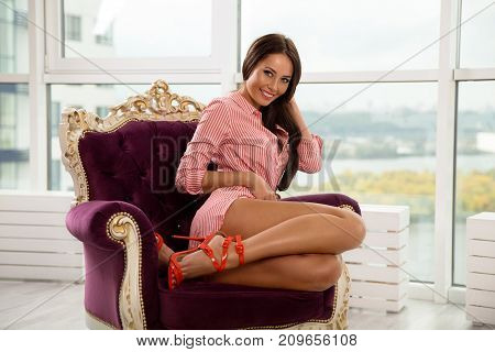 Beautiful smiling woman with perfect legs posing on the armchair in red striped shirt and high heels. Beauty portrait.