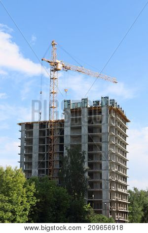 Tall crane works near tall residential building on construction site at summer day