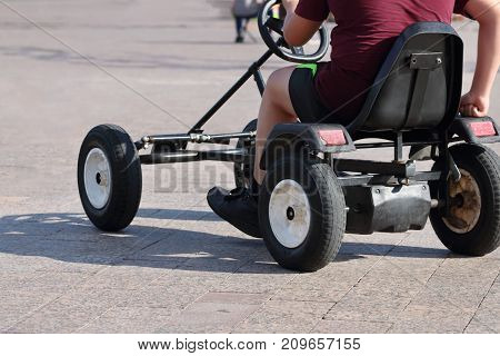 Man riding on foot-operated four-wheeler at sunny day noface back view