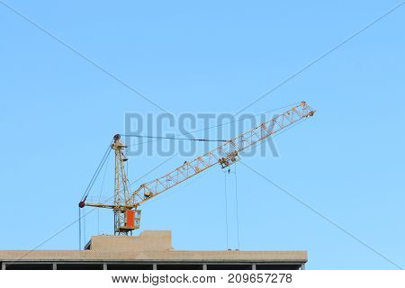 Big yellow stationary hoist on construction site part of building blue sky