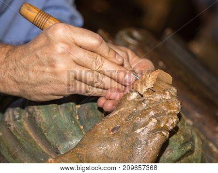 Restoring Wooden Sculpture: Close-up of Restorer working on Religious Works poster