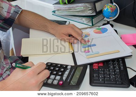 A businessman analyzing investment charts at his workplace and using his a computer stock chart cellphone. discussing the charts and graphs showing the results of their successful teamwork