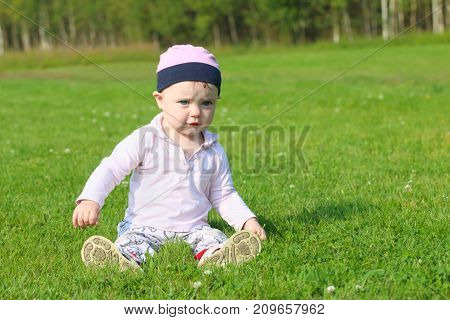 Cute happy baby girl in hat sits on green grass on summer field