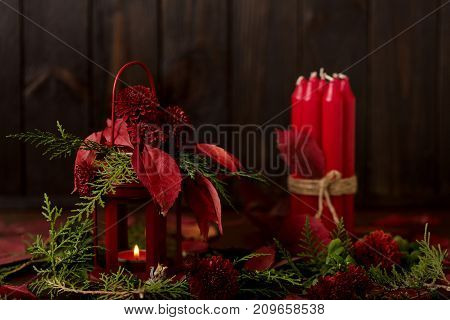 Still life on a dark background. Decor of candles and candlesticks with juniper daisies and red leaves. Selective focus.
