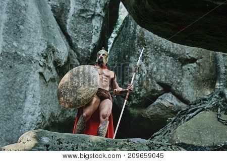 Full length low angle shot of a Spartan warrior with sexy muscular strong body posing on top of a rock armored looking away copyspace.