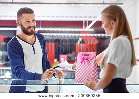 Handsome young bearded man at the jewellery store paying for his purchase with a credit card.