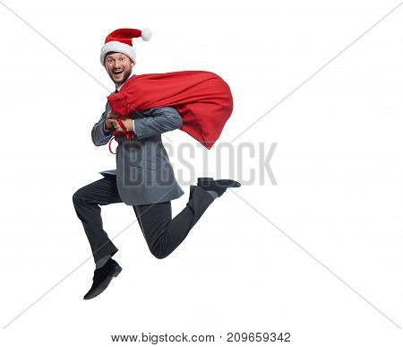 View of happy santa clause jumping up, smiling, looking at camera. Male in business suite and red cap, with big bag of presents and gifts. Concept of xmas holiday, new year party and winter holiday.