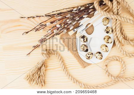 Palette With Quail Eggs And Decorations: Twigs Willow, Rope And Paintbrushes