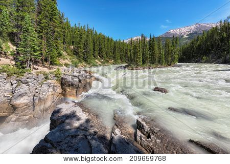 Small island and Sunwapta falls in Rocky Mountains, Jasper National Park, Alberta, Canada.
