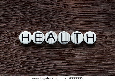 White round pills with inscription HEALTH on brown wooden board background