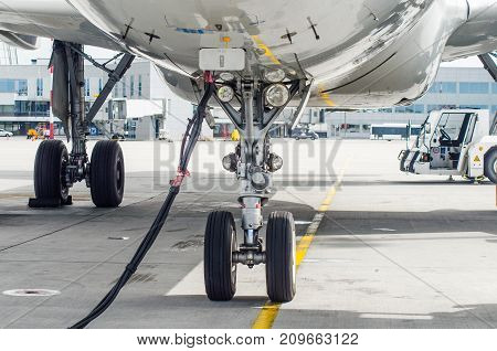 Front Landing Gear Of The Aircraft Landing Gear With Power Supply In The Airport Parking.