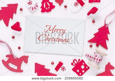 Christmas greeting card with inscription Merry Christmas! Composed of red Christmas decoration: toy rocking horse spruce mittens Santa's hat checkered ribbons and gift boxes on white background. Christmas wallpaper for websites social media business owner
