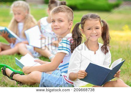 Cute little children reading books in park