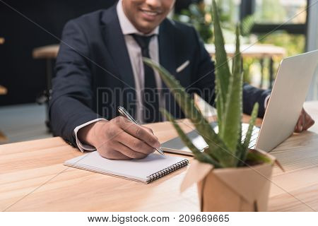 selective focus of smiling african american businessman writing in notebook at workplace