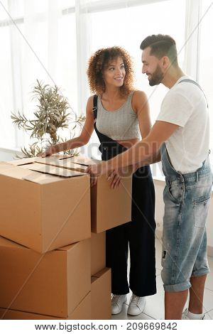 Newlyweds carry boxes in a new apartment.